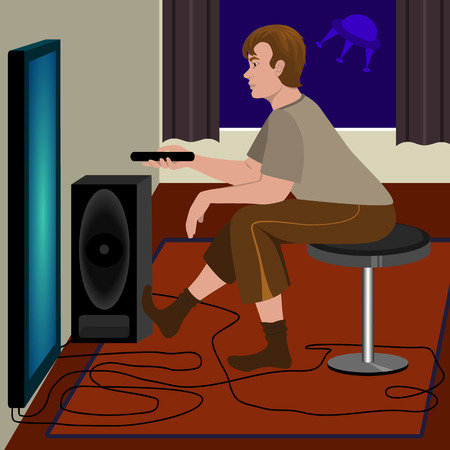 watching television: Young man sitting on a chair watching television