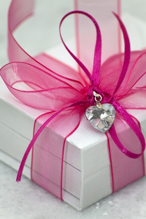 A white box tied with a pink satin ribbon bow. A gift for Christmas, Birthday, Wedding, or Valentines day. Isolated on white with clipping path.