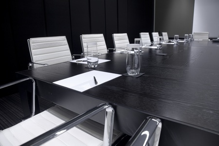 Meeting room interior with table, raw of chairs and block-notes,decorated in black and white tones