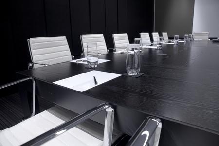 Vergaderzaal interieur met tafel, rauw van stoelen en block-notes, ingericht in zwarte en witte tinten