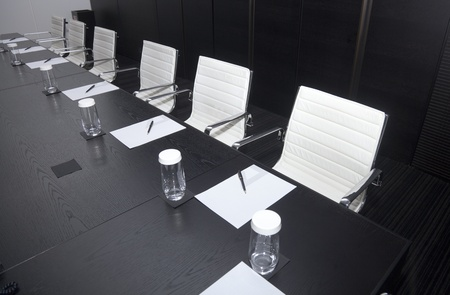 Meeting room interior with table, raw of chairs and block-notes,decorated in black and white tones photo