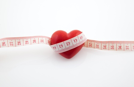 Red heart surrounded by a tape measure on white background
