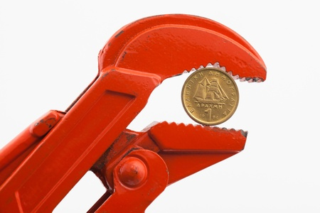 Financial crisis, drahma (old Greek coin) in press, economy concept. Orange wrench pressing a drahma coin