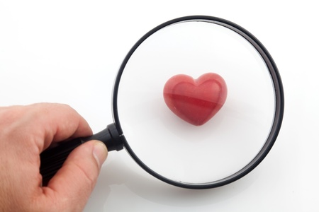 Looking a red heart through a magnifying glass Stock Photo