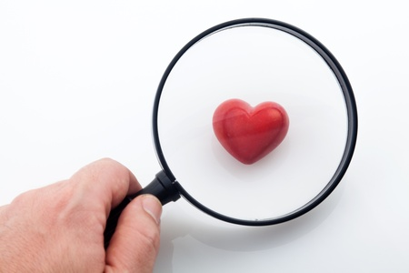 detect: Looking a red heart through a magnifying glass Stock Photo