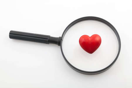 Looking a red heart through a magnifying glass photo