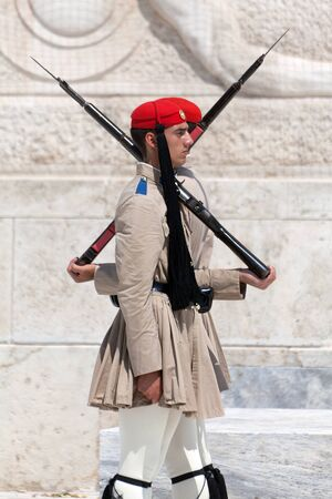 ATHENS, GREECE - JULY 23: Evzones (presidential guards) watches over the monument of the Unknown Soldier in front of the Greek Parliament Building at Syntagma Square on July 23, 2010 in Athens, Greece. Evzoni, is the name of historical elite mountain unit Stock Photo - 13337792