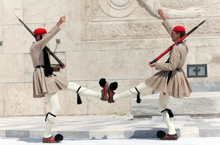 ATHENS, GREECE - JULY 23: Evzones (presidential guards) watches over the monument of the Unknown Soldier in front of the Greek Parliament Building at Syntagma Square on July 23, 2010 in Athens, Greece. Evzoni, is the name of historical elite mountain unit Stock Photo - 13337789