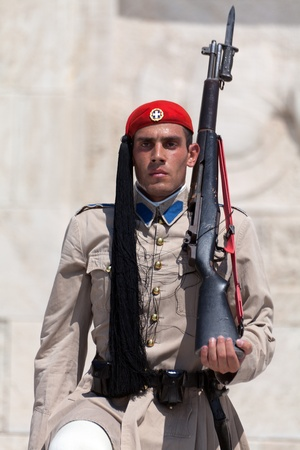 ATHENS, GREECE - JULY 23: Evzones (presidential guards) watches over the monument of the Unknown Soldier in front of the Greek Parliament Building at Syntagma Square on July 23, 2010 in Athens, Greece. Evzoni, is the name of historical elite mountain unit