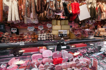 exists: BARCELONA, SPAIN - APRIL 14: Jamon market in La Boqueria market on April 14, 2012 in Barcelona, Spain. La Boqueria is one of the oldest markets in Europe that still exists. It was established in 1217. Editorial