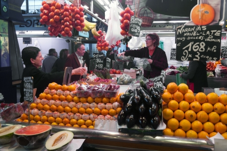 BARCELONA, SPAIN - APRIL 14: Unidentified tourists in famous La Boqueria market with Jamon, vegetables and fruits on April 14, 2012 in Barcelona, Spain. One of the oldest markets in Europe that still exist. Established 1217.