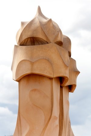 BARCELONA, SPAIN ? APR 14: Chimneys like masked soldiers on the roof of La Pedrera or Casa Mila designed by Antoni Gaudi, on April 14, 2012 in Barcelona, Spain. La Pedrera was built in 1906-1910.