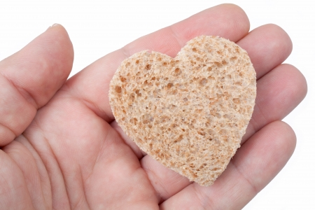 recieving: Food with love - helping the poor concept. Ηands holding a heart of bread Stock Photo