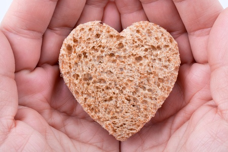 Food with love - helping the poor concept. Ηands holding a heart of bread Stock Photo - 14365194