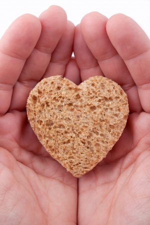 Food with love - helping the poor concept. Ηands holding a heart of bread