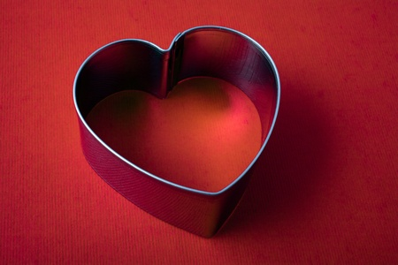 A vintage metal heart shaped sugar dough cookie cutter on red background photo