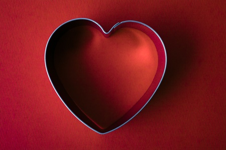 A vintage metal heart shaped sugar dough cookie cutter on red background Stock Photo - 14365166