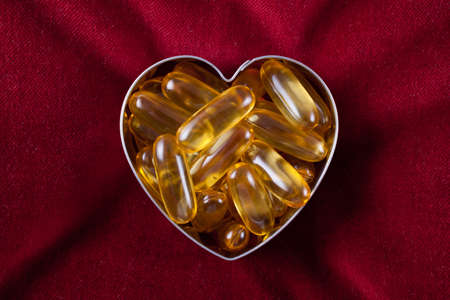 Vitamin capsules arranged in the shape of a heart to portray the concept of a healthy heart and lifestyle photo