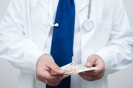 hospital fees: A portrait of a doctor with patients money in his hands Stock Photo
