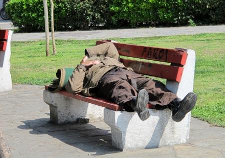 to degrade: SAL�NICA, GRECIA - 29 de marzo: El dormir sin techo en el banco en un parque p�blico el 29 de marzo de 2012 en Sal�nica, Grecia. Aumento del 25% de las personas sin hogar en los a�os 2009-2011 en Grecia