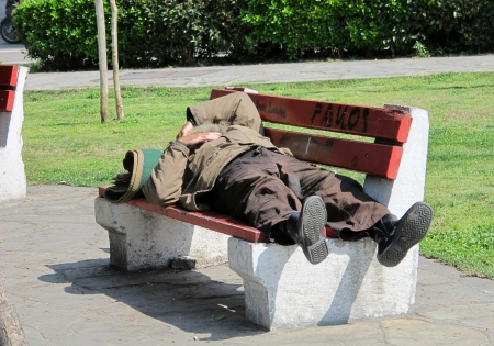 vagabond: THESSALONIKI, GREECE - MARCH 29: Sleeping homeless man on the bench in a public park on March 29, 2012 in Thessaloniki, Greece. Increase of 25% of the homeless in years 2009-2011 in Greece