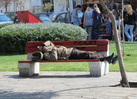 mendicant: THESSALONIKI, GREECE - MARCH 29: Sleeping homeless man on the bench in a public park on March 29, 2012 in Thessaloniki, Greece. Increase of 25% of the homeless in years 2009-2011 in Greece