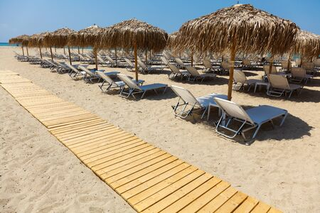 Beautiful beach with deck chairs and umbrellas on the sandy beach in Nea Irakleia  Halkidiki   Thessaloniki - Greece Stock Photo