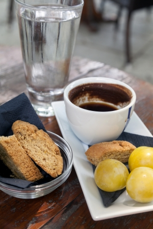Greek coffee and cookie  In backgrounds fruits and glass of water  Typical beverage greek and turkish  Taken in Pelion - Greece photo