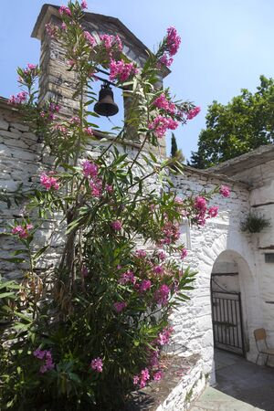 Church with steeple and flowers in the Greece photo