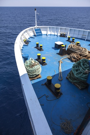 Bow of mid-sized passenger ferry boat showing the anchoring machinery on a trip. Blue ocean water in Mediterranean sea photo