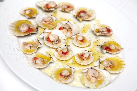 open topped: Open scallops, topped with salt and pepper on a white plate Stock Photo