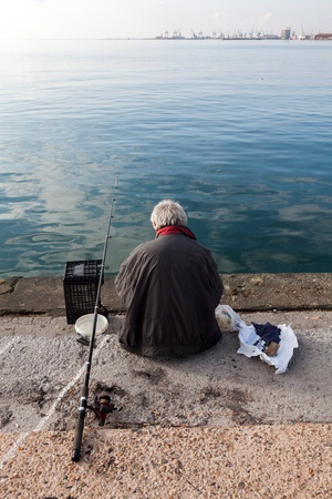 insist: THESSALONIKI, GREECE - NOVEMBER 22: Allthough Thermaikos Gulf has been heavily contaminated  by seawage, fishermen still insist to fish there on November 22, 2012 in Thessaloniki, Greece