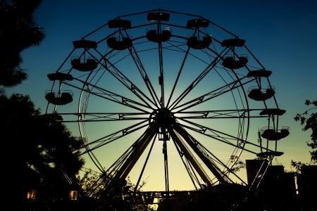 Ferris wheel silhouette over sun
