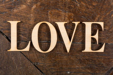 Wooden letters forming word LOVE written on old vintage wooden plates with space for your own text. photo