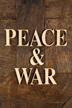 Wooden letters forming words PEACE & WAR written on old vintage wooden plates  photo