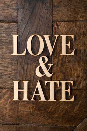 Wooden letters forming words LOVE & HATE written on old vintage wooden plates  photo