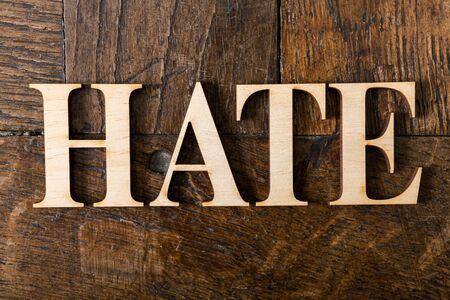 Wooden letters forming word HATE written on old vintage wooden plates  photo