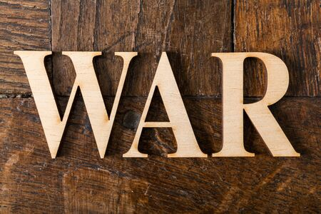 Wooden letters forming word WAR written on old vintage wooden plates photo