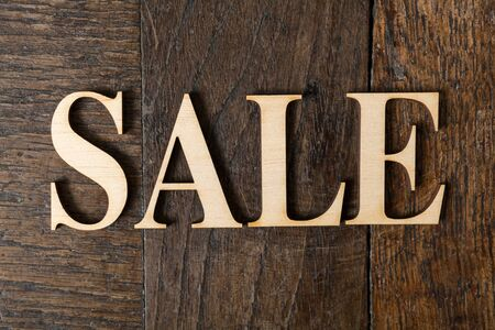 Wooden letters forming word SALE written on old vintage wooden plates photo