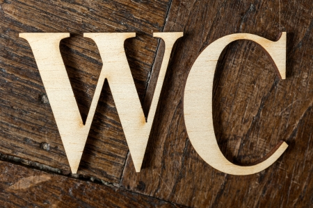Wooden letters forming word WC written on old vintage wooden plates