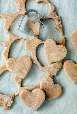 cookie cutter: Heart shaped cookie cutter on raw cookie dough with a few cookies
