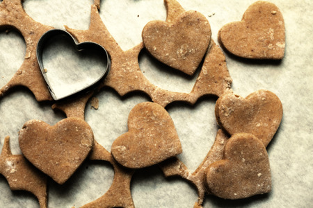 cookie cutter: Heart shaped cookie cutter on raw cookie dough with a few cookies. Vintage view Stock Photo