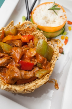 carot: Chinese dish; chicken with sweet green peppers in a fried noodle nest and steamed rise decorated with cucumber and carot aside   Stock Photo