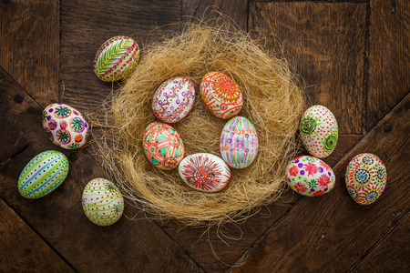 Hand painted colorful Easter eggs in nest on rustic wooden planks   photo