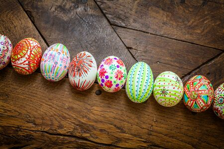 Hand painted colorful Easter eggs on rustic wooden planks   photo