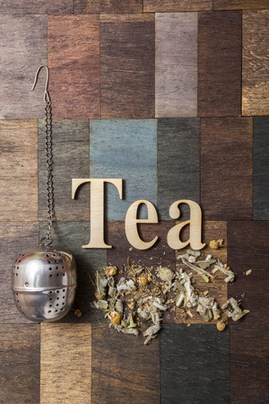 tea infuser: Tea time words, Tea Infuser and dry mountain tea leaves on wooden background Stock Photo