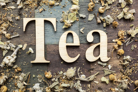 infuser: Tea time words and dry mountain tea leaves on wooden background Stock Photo