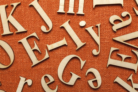 Wooden alphabet letters on orange fabric surface with space for your own text. photo