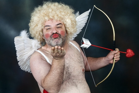 Fat bearded mature hairy cupid with bow and heart arrow. Sending a kiss Banque d'images