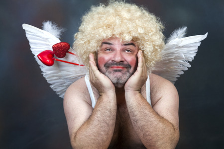 Fat bearded mature hairy cupid with bow and heart arrow.